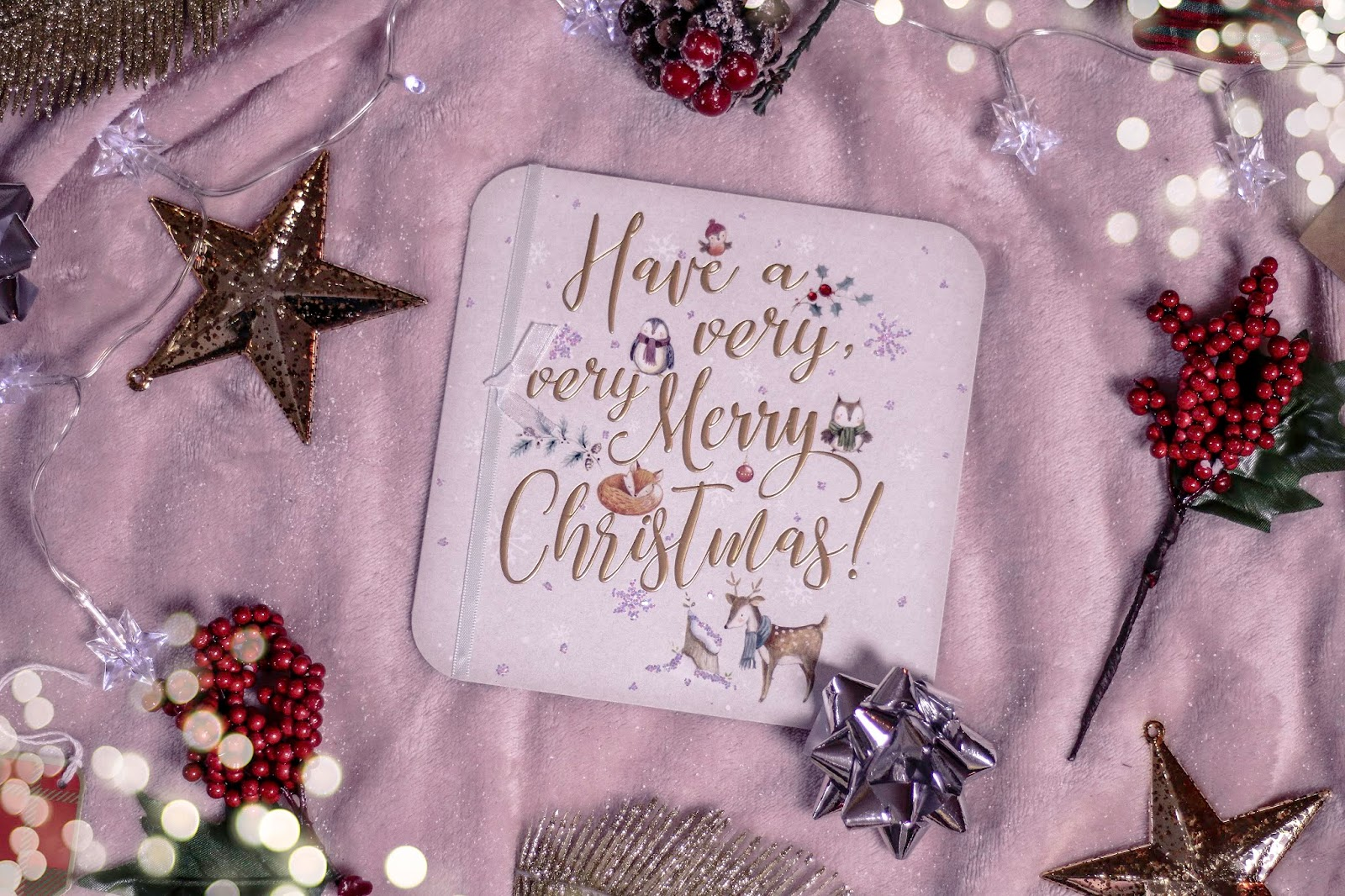 "Close up of a Christmas card that says ""Have a very very merry Christmas"" on the front in gold with little drawings of a penguin, robin and deer on the front. The card has a white background and white ribbon running down the front with a bow. The card is on a pink blanket with gold and silver christmas decorations surrounding the card. A flat lay photo taken from directly above."