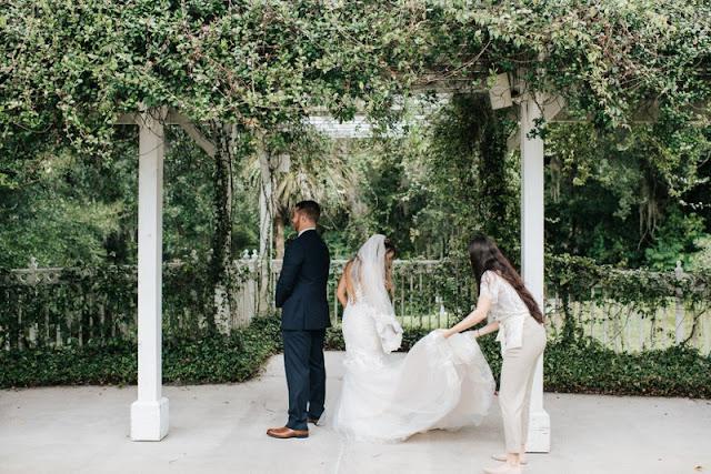 wedding planner helping bride with dress