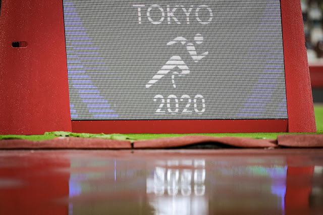 Placa de Tóquio 2020 em campo do Estádio olímpico com muita chuva