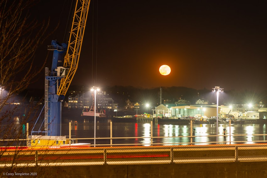 Portland, Maine USA April 2020 photo by Corey Templeton. The full moon from earlier this month, rising over the Casco Bay Bridge and South Portland.