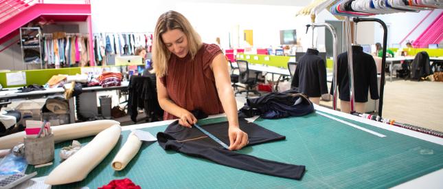 Technical designer measuring a garmet