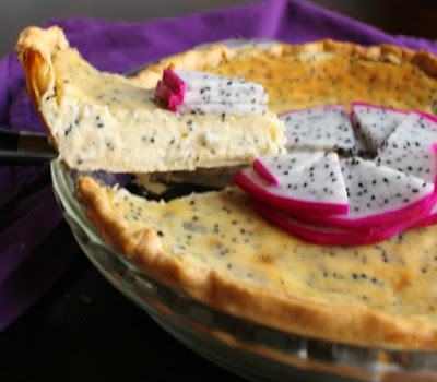 first slice of dragon fruit pie being lifted out of pie plate with creamy center dotted with black seeds showing