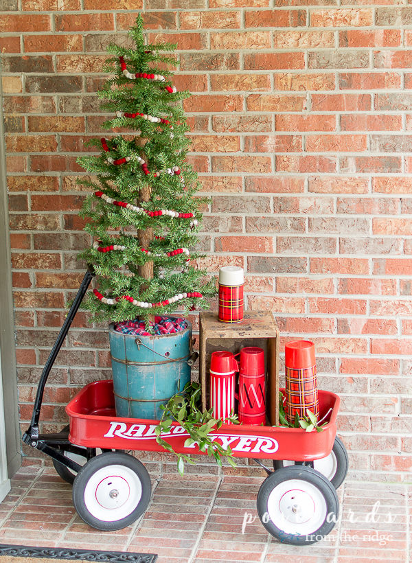 red wagon with vintage thermoses and old ice cream churn with Christmas tree