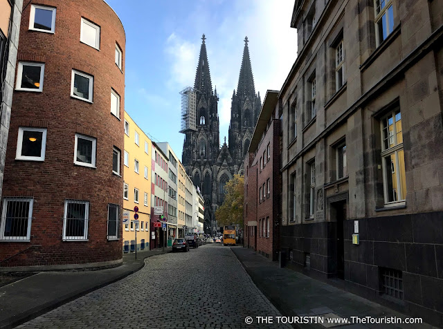 A cobblestone street between red brick and beige stone houses that leads to the massive stone cathedral on a square at the end of it.