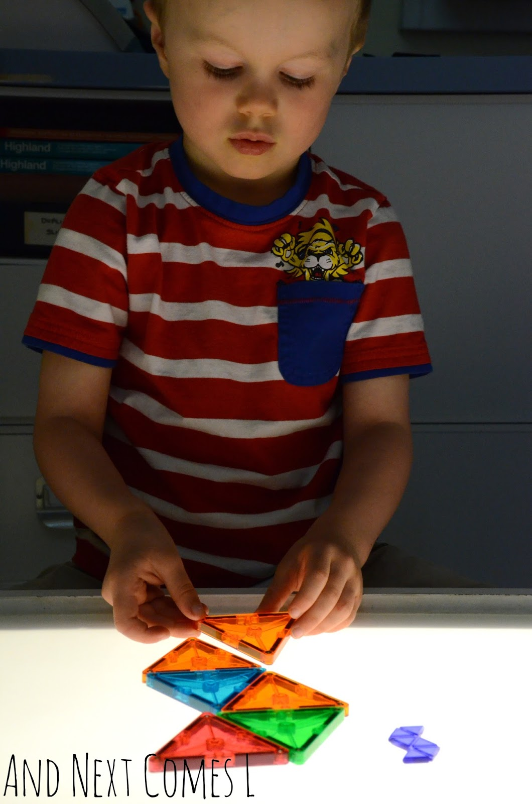 J recreating shapes on the light table using Magna-Tiles from And Next Comes L