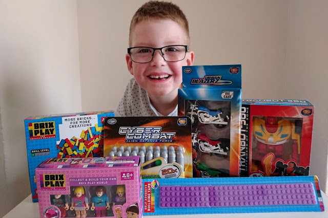 Boy with blonde hair wearing glasses and a white short sleeved t-shirt with small blue + signs on. He is smiling over a selection of toys inside their packaging. A range of toys including building bricks, foam darts, motor cycles and a transforming car which are sat on a table.