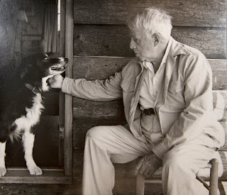 Robert Frost sitting at his house in Ripton petting Gillie the dog.