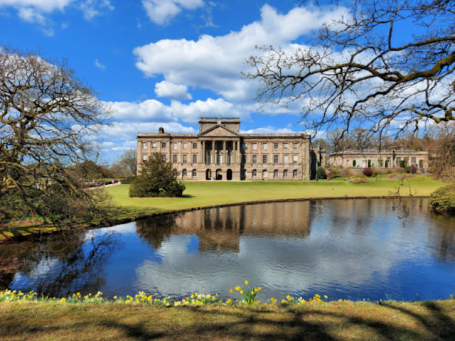 A stately home seen across a lake.  There are daffodils around the lake and a blue sky above