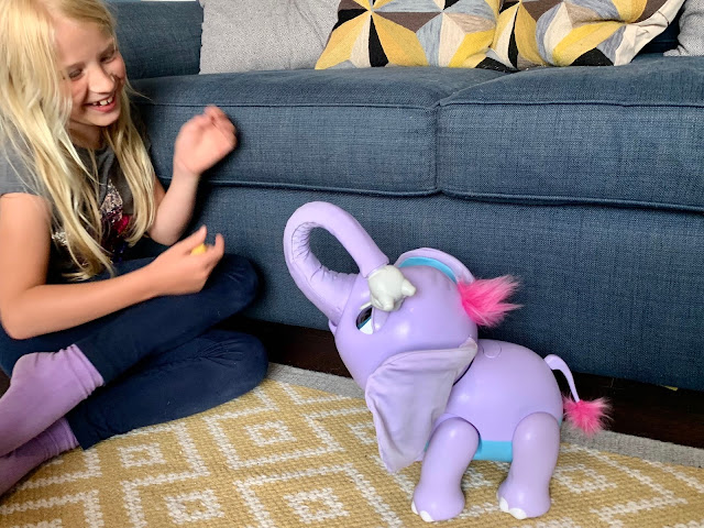 A 7 year old girl laughing at Juno Wildluvs elephant while playing with it for a review