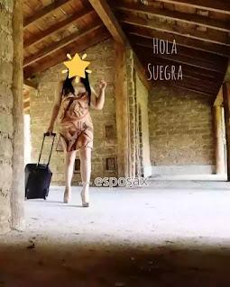 Nora llegando a una cabaña con maleta