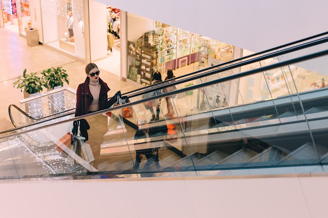 A lady going up the escalator at a mall.