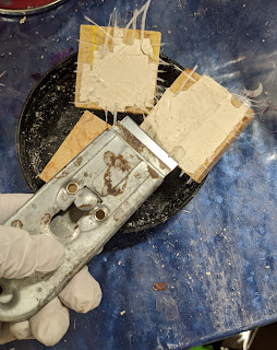 Three pieces of marble showing grout and fiberglass, plus gloved hand holding razor scraper tool.