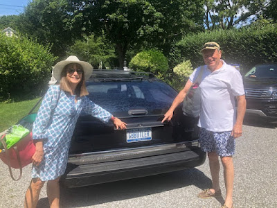 couple in beach wear ready to climb into a station wagon for a free trip to the beach