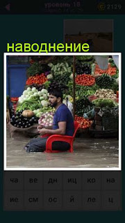 во время наводнения на стуле сидит мужчина а ноги в воде и продает цветы
