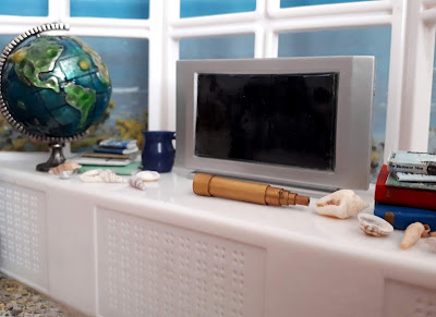 1/12 scale modern miniature windowsill over looking the sea. On the windowsill is a globe, a flat-screen TV, a vintage telescope, several piles of books and a number of shells.
