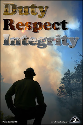 Duty, Respect, Integrity: Wildland firefighter kneeling before a smoke column