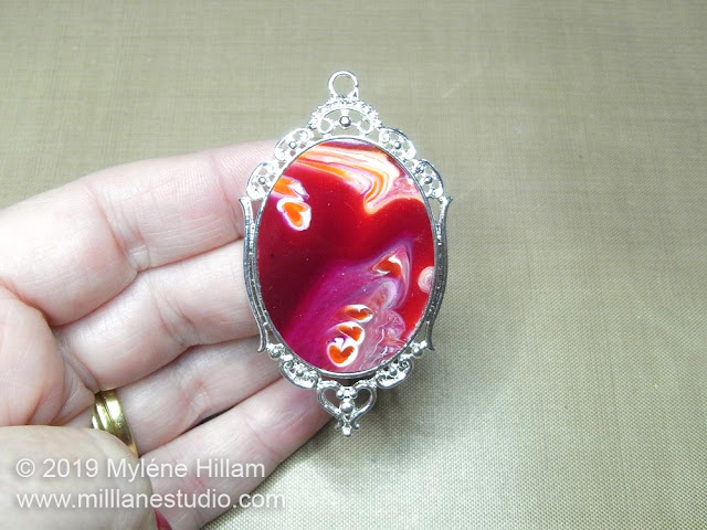 Burgundy and orange marbled resin pendant.