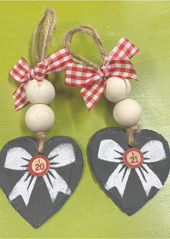 Two heart ornaments with stenciled bows