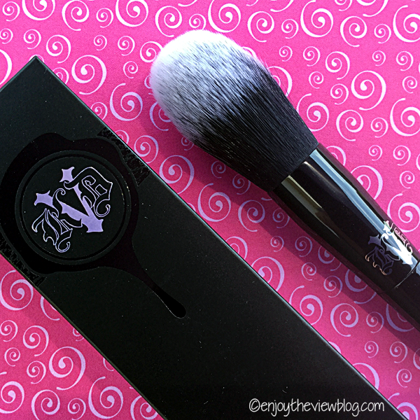 fluffy makeup brush on a pink background