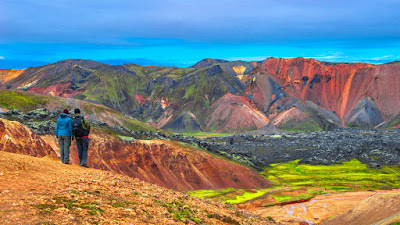 Two hikers overlooking colorful volcanic mountains in Landmannalaugar