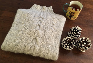 Cabled pullover knitted with DROPS Air folded and next to pinecones and a mug of tea