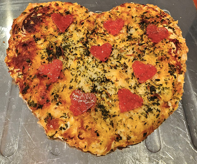 this is a heart shaped pizza with heart shaped pepperoni cut out on top
