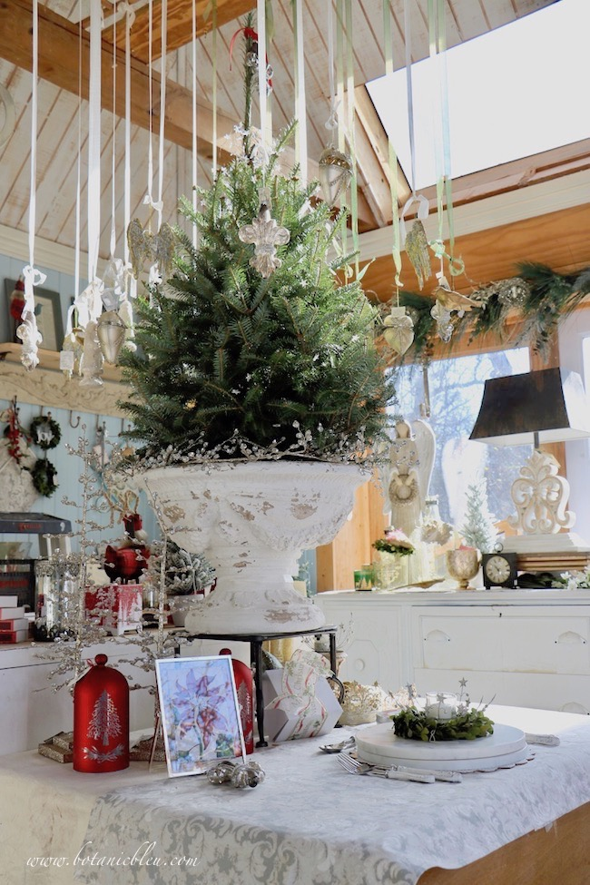 French Country Christmas Event 2019 has several Christmas ornaments hanging from the ceiling surrounding a fresh cut tree in a white pedestal urn
