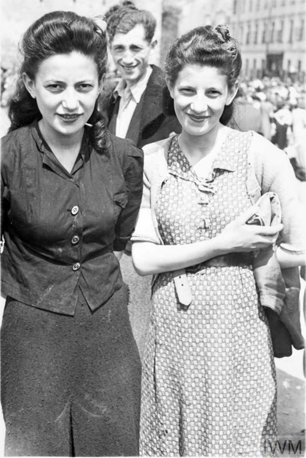 Two well dressed women, most likely sisters, posing for a photograph in a street market.