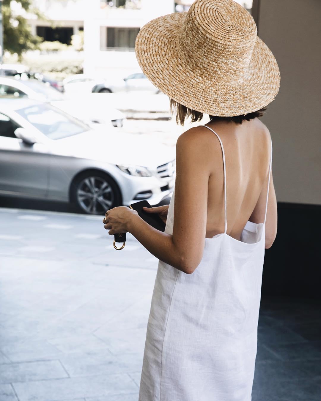 21 Breezy Sleeveless White Linen Dresses for Summer —Carmen Grace Hamilton Outfit Idea Minimalist Linen Dress and Straw Hat