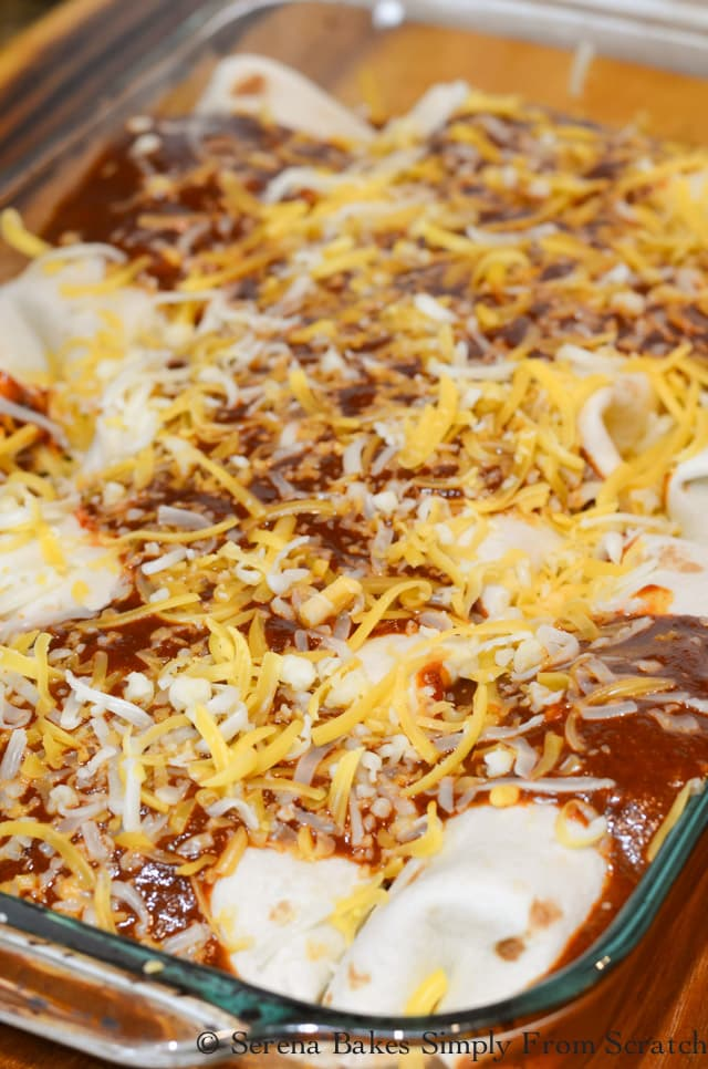 Steak Burritos covered with homemade enchilada sauce and shredded yellow and white cheese.