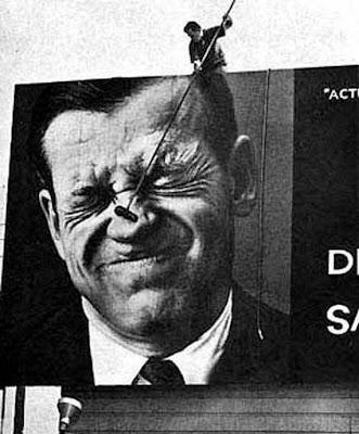 Homem colando anuncio com imagem franzindo o nariz
