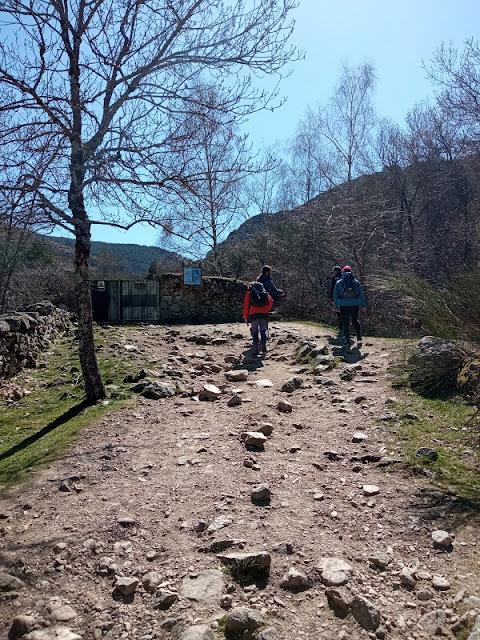 El sendero bordea la valla por la derecha, juntándose al río