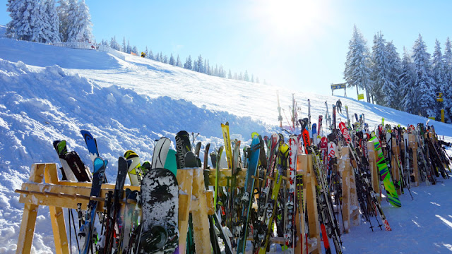 lots of skis standing up against a fence at the bottom of the hill