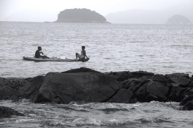 Nativos caiçaras em canoas, na Praia de Picinguaba, em Ubatuba.