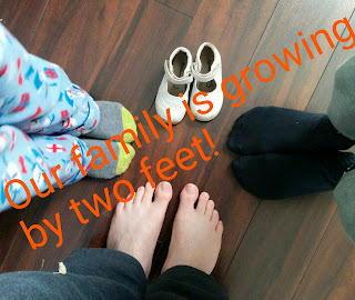 "Picture of three sets of feet and an empty pair of shoes with orange text across saying, ""our family is growing by two feet"" by OneQuarterMama.ca"