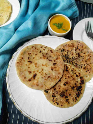 Serving onion kulcha in a plate, dal and papad in background