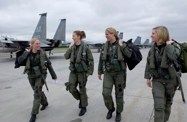 Four pilots walking with F-15 planes in the background.