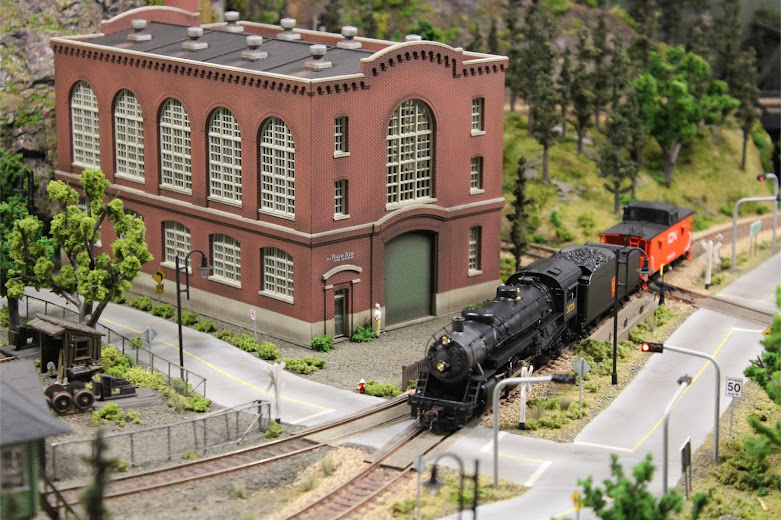A USRA Light Mikado 2-8-2 steam locomotive passing in front of a completed Walthers Northern Light & Power kit