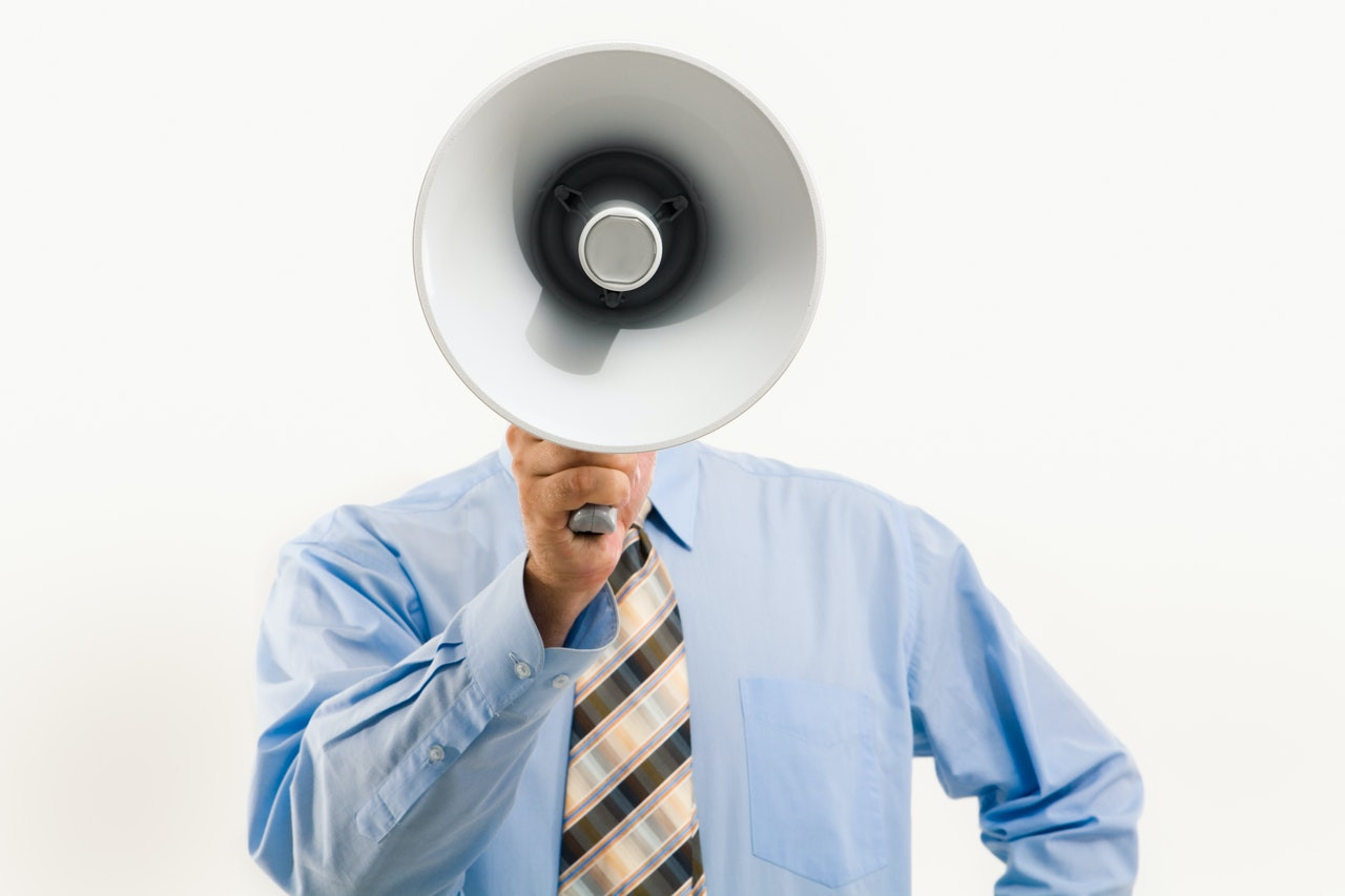 A man holding megaphone, signifying voice search optimization