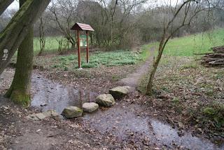 In einem kleinen Bach liegen mehrere große Steine hintereinander, die als Gehweg über den Fluss führen. Im Hintergrund sieht man eine Wiese, auf der eine hölzerne Infotafel mit Spitzdach steht.