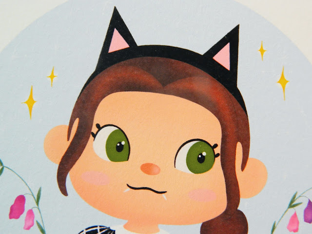 A photo of the head section of a cute art piece. A girl with green eyes and brown hair. She's wearing black cat ears