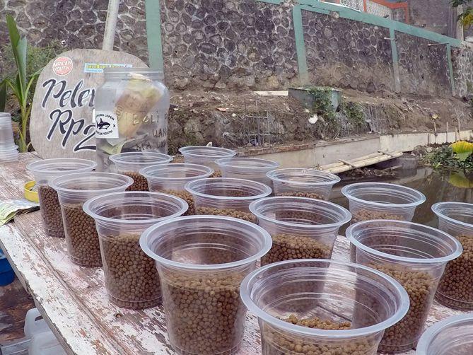 Penduduk setempat menjual pakan ikan