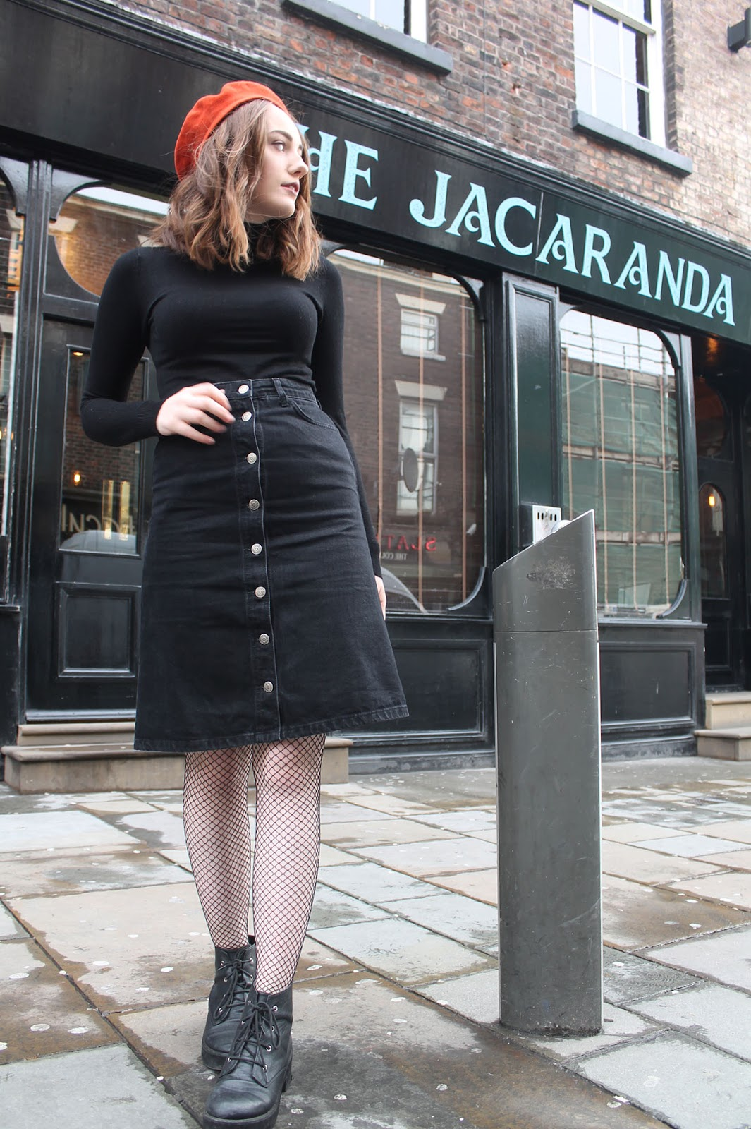 60s inspired outfit including orange Mary Quant beret, black polo neck jumper, black denim button up midi skirt, fishnet tights and black lace up boots