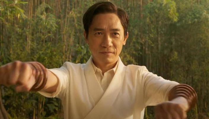 Imagem: o personagem Wenwu, interpretado por Tonny Leung, um homem asiático de meia idade, com cabelos pretos curtos e rentes, com uma camisa branca e nos braços aros metálicos e com um punho fechado em posição de luta, ao fundo uma floresta de bambus.