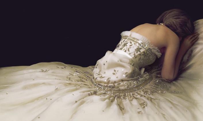 Imagem de capa: detalhe do pôster oficial do filme, um fundo preto com a figura de princesa Diana, de costas, encostada no que parece ser uma cama, em um vestido luxuoso de cor perolada e rodeada por uma enorme saia do vestido.
