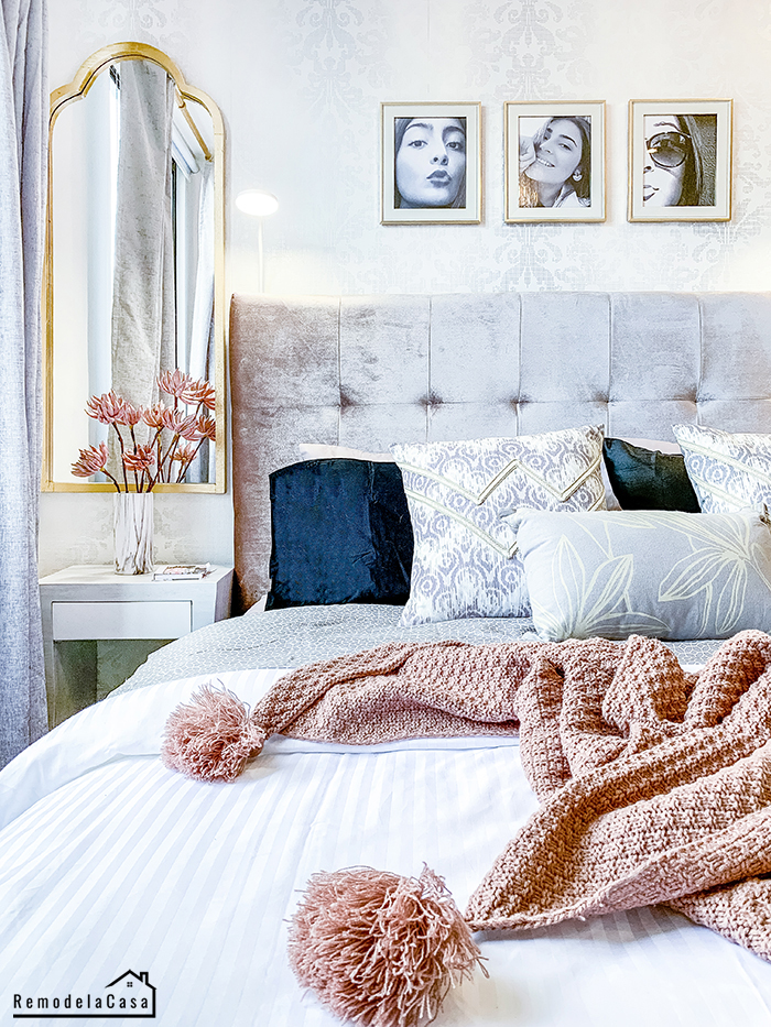 a glam bedroom with silver wallpaper, drapes, Moroccan style mirrors and a dash of pink
