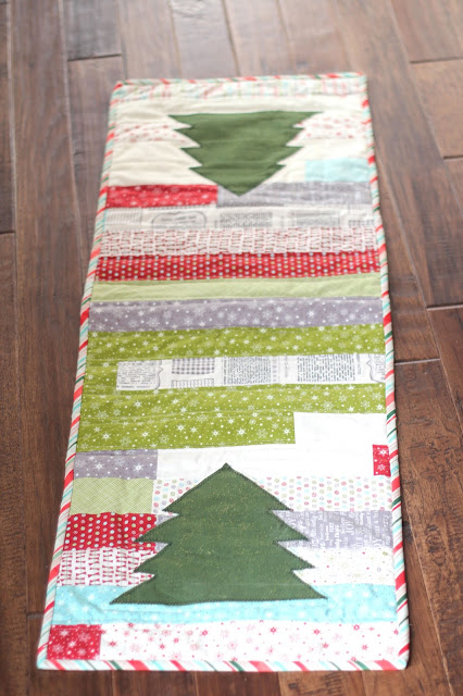 Christmas quilted table runner using Jelly Rolls and appliques