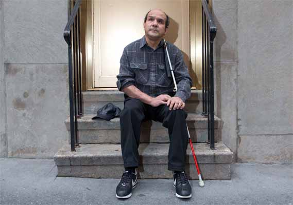 A blind man siting on a stairs with his walking stick in his hands