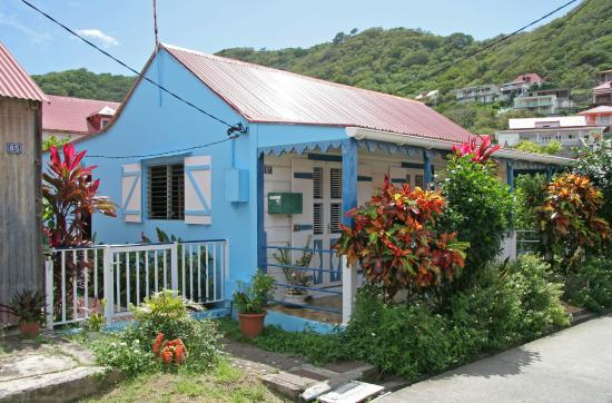Maison créole en bois avec toiture en tôle rouge et petit jardin