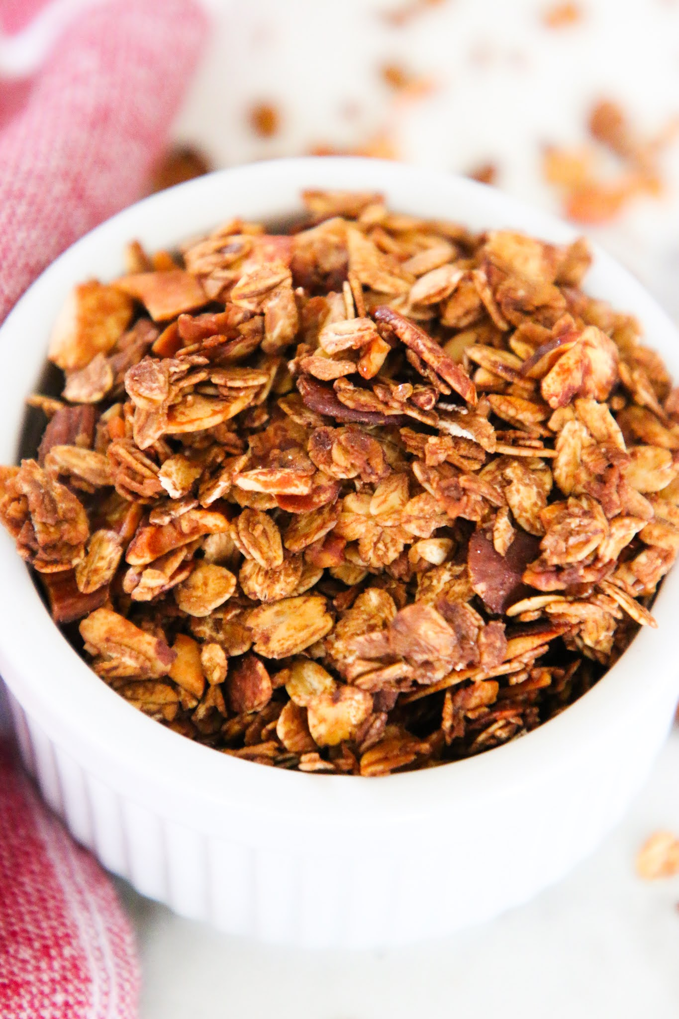 Granola in a small white bowl with granola scattered on the table with a red dish towel.